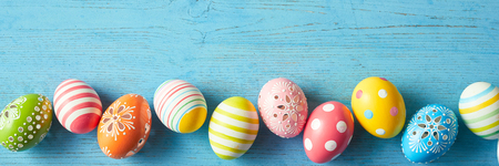 Photo for Panorama banner with a border of colorful decorated Easter eggs with stripes, polka dots and flowers on a blue wood background with copy space - Royalty Free Image