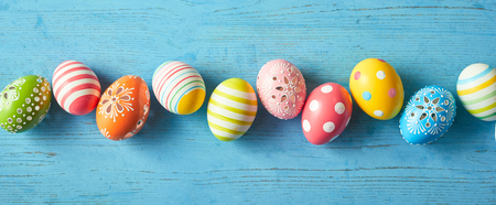 Photo for Row of colorfully painted Easter eggs on blue wooden background, wide angled image. - Royalty Free Image
