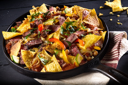 Photo for Tender spicy beef entrecote steak with red hot chili peppers, nachos and a topping of cheese and fresh coriander served in an old iron skillet in a high angle view - Royalty Free Image