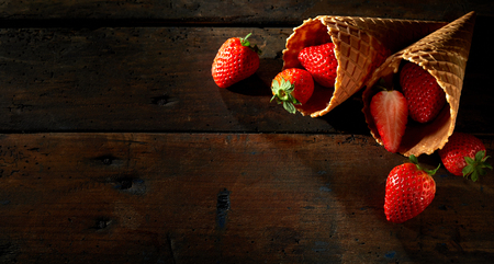 Photo for Cornets filled with ripe red strawberries spilling out onto a rustic wood surface with copy space in a wide angle format - Royalty Free Image