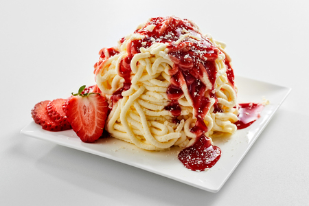 Foto de Plate with spaghetti ice cream dessert with sweet strawberry topping - Imagen libre de derechos