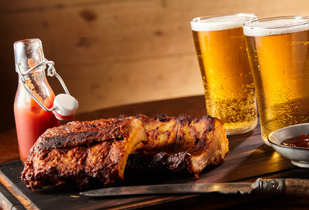 Photo pour Spicy seasoned grilled spare ribs with two tall glasses of cold beer served with ketchup and chutney on a tray in a tilted angle - image libre de droit