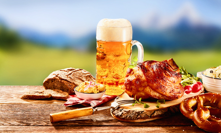 Foto de Traditional German cuisine, Schweinshaxe roasted ham hock, pretzel with obatzter cheese spread and glass of pale beer on wooden table - Imagen libre de derechos