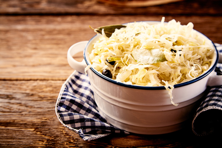 Foto de Bowl of sauerkraut cabbage on dishcloth against wooden table - Imagen libre de derechos