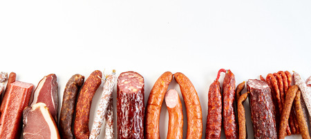 Photo pour Panorama banner with a diversity of spicy dried, cured or smoked sausages arranged as a bottom border with copy space on white - image libre de droit