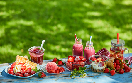 Photo for Fresh, healthy, vibrant summer strawberry smoothie bowl, juices and desserts picnic on a bright outdoor table setting. - Royalty Free Image