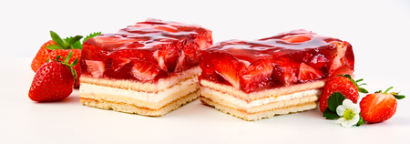 Photo for Two slices of strawberry and cream layer cake or tart topped with fresh ripe fruit in a syrup in a panorama banner on white - Royalty Free Image