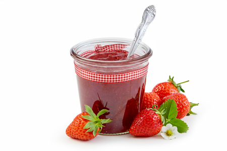 Foto de Jar of fresh strawberry jam or puree tied with checkered textile ribbon and surrounded by ripe berries isolated on white - Imagen libre de derechos