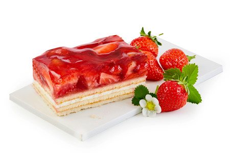 Foto de Delicious freshly baked layer cake topped with strawberries served on a white board with fresh whole fruit isolated on white - Imagen libre de derechos