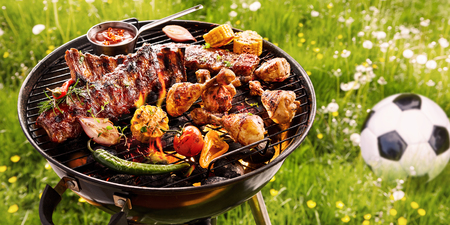 Photo for Summer or spring barbecue outdoors in a meadow with dandelions and a soccer ball with assorted vegetables, spicy spare ribs and chicken legs grilling on the fire - Royalty Free Image