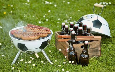 Photo pour Bratwurst sizzling on the grill at a Soccer themed BBQ with ball shaped barbecue and crate full of bottles of craft beer in a green field - image libre de droit