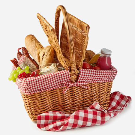 Foto de Summer picnic basket filled with food with fresh fruit and juice, spicy salami, baguettes, tomatoes and herb spread isolated on white on a rustic checked tablecloth - Imagen libre de derechos
