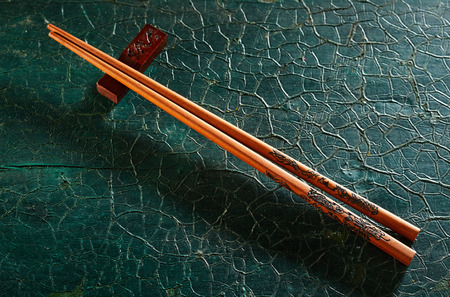 Photo pour Pair of chopsticks on a rest over weathered textured green wood placed diagonally with copy space viewed from above - image libre de droit