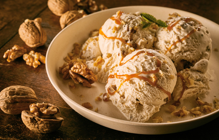 Foto de High Angle Close Up Still Life of Scoops of Maple Walnut Ice Cream Drizzled with Caramel Sauce and Garnished with Walnuts in Large Bowl on Wooden Table - Imagen libre de derechos
