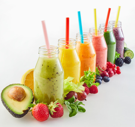 Photo pour Receding diagonal row of different fresh fruit and vegetable smoothies with colourful ripe ingredients on white with copy space for a healthy nutritious diet - image libre de droit