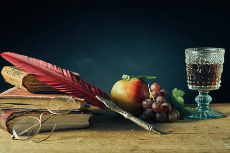 Photo for Vintage still life for college or a writer with a feather quill pen and reading glasses resting on old books alongside fresh grapes, an apple and goblet of wine on an old wooden table with copy space - Royalty Free Image