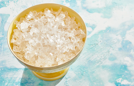 Photo for Yellow bowl of crushed clean ice for use as an ingredient in cooking or beverages over a cool mottled blue background with copy space - Royalty Free Image