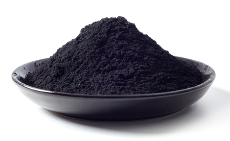 Photo pour Dish heaped with food grade pulverised black charcoal used as an additive in food and drink for detoxification and cleansing of the body - image libre de droit