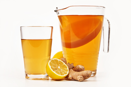 Foto de Jug and glass filled with fresh kombucha made with fermented sweetened black tea and served with lemon and root ginger over white viewed from the side - Imagen libre de derechos