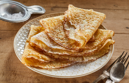 Foto de Crispy golden fried pancakes or griddle cakes on a plate dusted with castor sugar and stacked for a scrumptious breakfast or dessert - Imagen libre de derechos