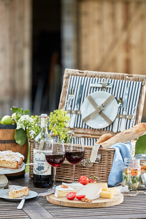 Photo pour Vintage picnic hamper with wine, bread, cheese platter and freshly baked tart for dessert on a table in the garden - image libre de droit