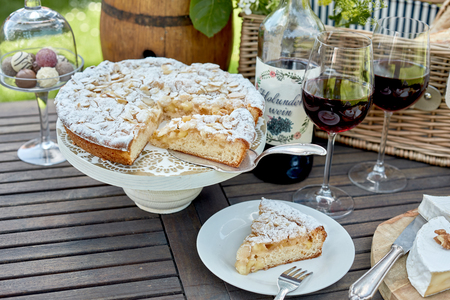 Photo pour Sliced freshly baked cake or tart for a picnic dessert served on a wooden outdoor table with glasses of red wine and chocolate bonbons - image libre de droit