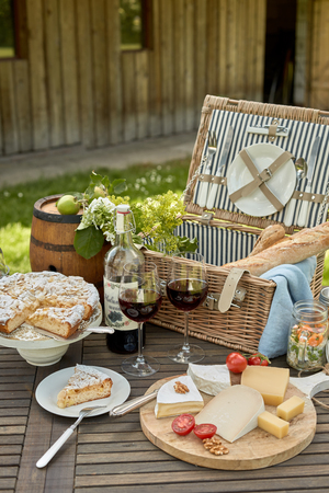 Photo pour Selection of cheese on a platter with red wine served on an outdoor table with a picnic hamper and a freshly baked sliced cake for dessert - image libre de droit