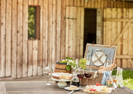 Photo pour Gourmet picnic hamper served al fresco on a rustic garden table in front of a wooden cabin with cake, cheese platter, pickles baguettes and red wine, copy space alongside - image libre de droit