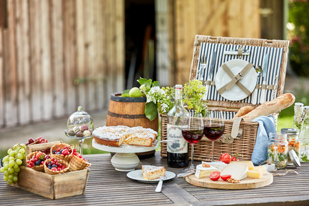 Photo pour Tasty summer picnic al fresco on a garden table with red wine, fresh berries and fruit, cheese platter, baguettes, pickles and cake for dessert - image libre de droit
