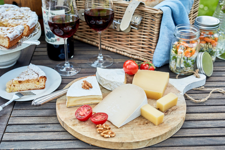 Photo pour Selection of cheese on a cheeseboard at a picnic on a wooden outdoor table with a wicker hamper, pickles, freshly baled cake for dessert and glasses of red wine - image libre de droit