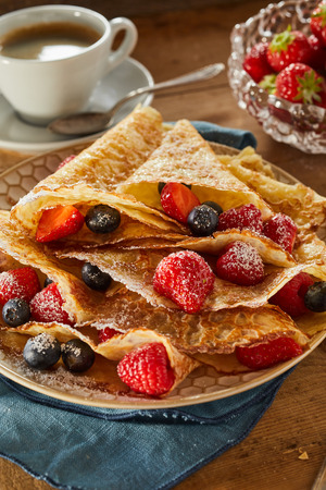Foto de Crispy golden fried crepes filled with assorted fresh ripe berries including strawberries, raspberries and blueberries in a close up view for menu advertising - Imagen libre de derechos