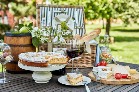 Photo pour Assorted desserts and cheeses on plates next to picnic basket on rustic wooden table in bright sunlit meadow during summer season - image libre de droit