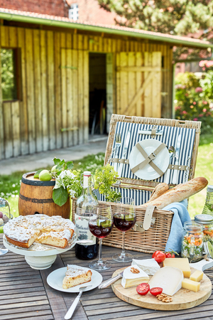 Photo pour Gourmet picnic hamper served outdoors on a garden table with a selection of cheeses, red wine, pickles, bread and freshly baked tart for dessert - image libre de droit