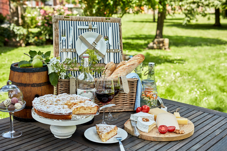 Photo pour Gourmet picnic lunch under a tree in a park laid out on a wooden slatted table with a hamper, bread, cheese, wine, chocolates and tart for dessert - image libre de droit