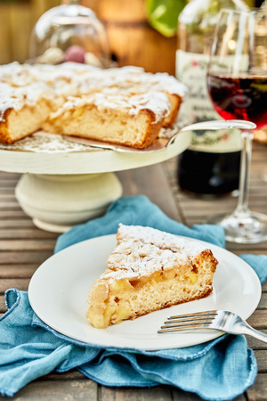 Photo pour Freshly baked slice of tart on a plate outdoors on a picnic table with glasses of red wine in a close up view - image libre de droit