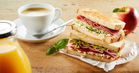 Foto de Cup of coffee, apple and double sandwich with ham on table - Imagen libre de derechos
