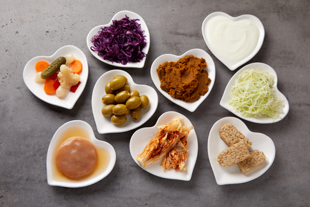 Photo for Assorted fermented foods viewed from above in heart-shaped dishes with yogurt, beet, suaerkraut, scoby, pickles, miso and olives rich in probiotics and microorganisms essential for a healthy gut - Royalty Free Image