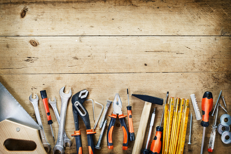 Photo pour Bottom border of assorted hand tools arranged in a neat row conceptual of DIY, renovations, repair, building and woodworking over wood with copy space and vignette - image libre de droit
