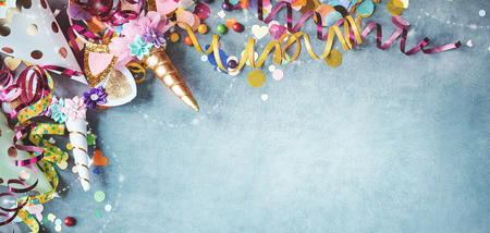 Foto de Panorama unicorn banner with festive carnival border of colorful streamers, party hats, candy over a cool blue textured background with copy space - Imagen libre de derechos