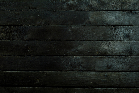 Photo pour Blacked charred wood panel background texture burned in a fire for BBQ concepts in a full frame view - image libre de droit