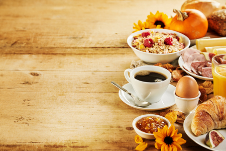 Photo pour Seasonal autumn Intercontinental breakfast border with a variety of fresh food and beverages, sunflowers and pumpkins on a rustic wood background with copy space - image libre de droit