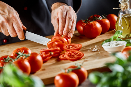 Foto de Chef slicing fresh ripe tomatoes on a chopping board surrounded by ingredients for Italian and Mediterranean cuisine in a close up on his hands - Imagen libre de derechos