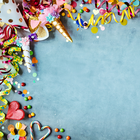 Foto de Carnival border with colorful party hats, candy and streamers on a texture blue background with copy space in square format - Imagen libre de derechos