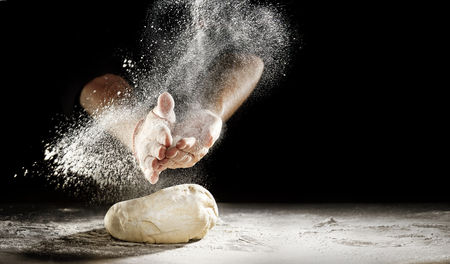 Photo pour Pastry chef clapping his hands to dust a mound of freshly prepared pastry with flour in a freeze motion of a cloud of flour midair on black with copy space - image libre de droit