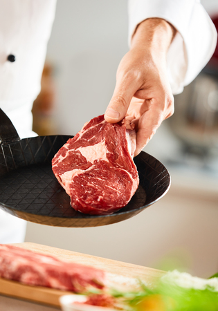 Photo for Chef placing a fresh uncooked ribeye steak in a pan ready for cooking in a close up view on his hand - Royalty Free Image
