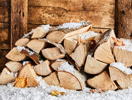 Photo for Winter woodpile outside a rustic wooden house covered in a fresh coating of snow and colorful autumn leaves - Royalty Free Image
