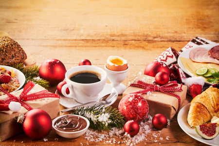 Photo pour Intercontinental Christmas breakfast spread with espresso, croissant, cheese, meat, bread and cereal interspersed with colorful Xmas decorations, gifts and snow - image libre de droit