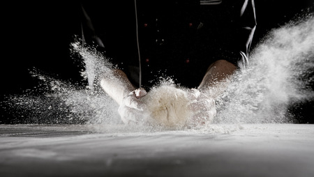Foto de Restaurant worker slamming dough on table causing white powdery flour to spray into the air in long streaks - Imagen libre de derechos