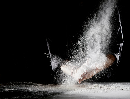 Photo pour Cloud of flour spraying into air and spilling onto flat table surface as man wearing black chef outfit rubs hands - image libre de droit