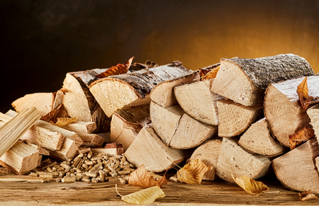 Photo for Stack of light colored wood logs sitting on top of brown wooden table in front of orange and black background - Royalty Free Image